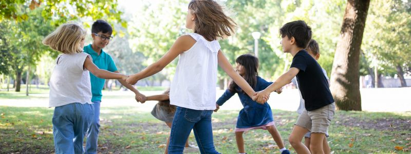 Group of children holding hands and dancing around, enjoying outdoor activities and having fun in park. Kids party or friendship concept